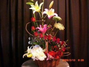 elegante canasta en espiral de rosas lilis y lisiantus1200 pwesos